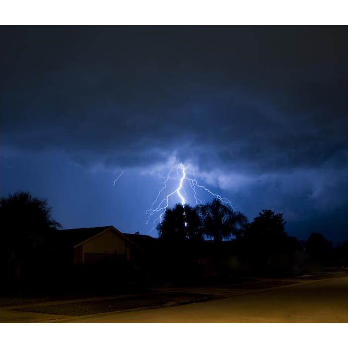 lighting striking hillside during storm at night
