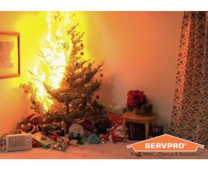Christmas tree on fire with presents under the tree. With SERVPRO house logo on bottom corner.